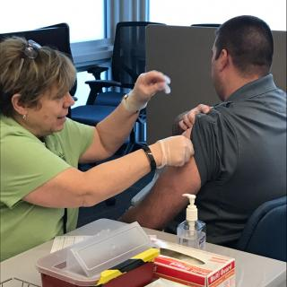 A Public Health Nurse from the St. Louis County Health Department Administers a Tetanus Vaccine.